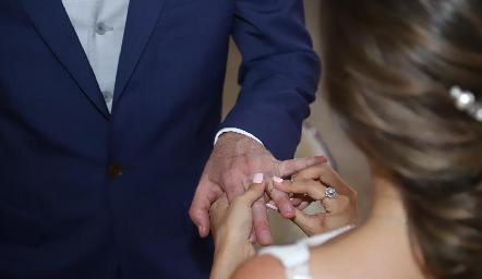 Claudia colocándole la alianza matrimonial a Alejandro.